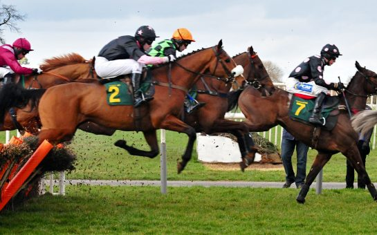 Horseracing image of race with horses travelling over a jump