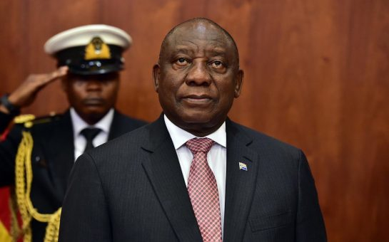 President of South Africa, Cyril Ramaphosa stands in front of a saluting soldier with a brown background behind them.