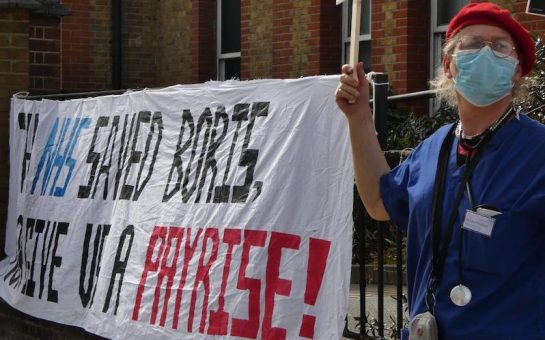 "Sarah Jane Baker cheers in front of protest banner reading ""THE NHS SAVED BORIS GIVE US A PAY RISE!"". She is wearing scrubs, a face-mask, a stethoscope and a red beret outside Lewisham Hospital."