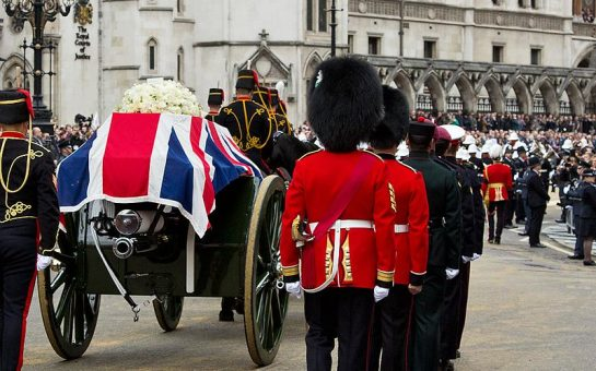 Queens guard accompanying a horse drawn carriage carrying a coffin draped in the Union Jack.