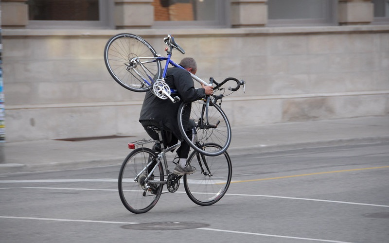 A man carries a bicycle over his shoulder as he rides away from the photographer on another bike