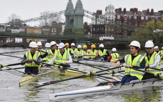 Rowers in hard hats and high-vis vests in front of closed Hammersmith Bridge