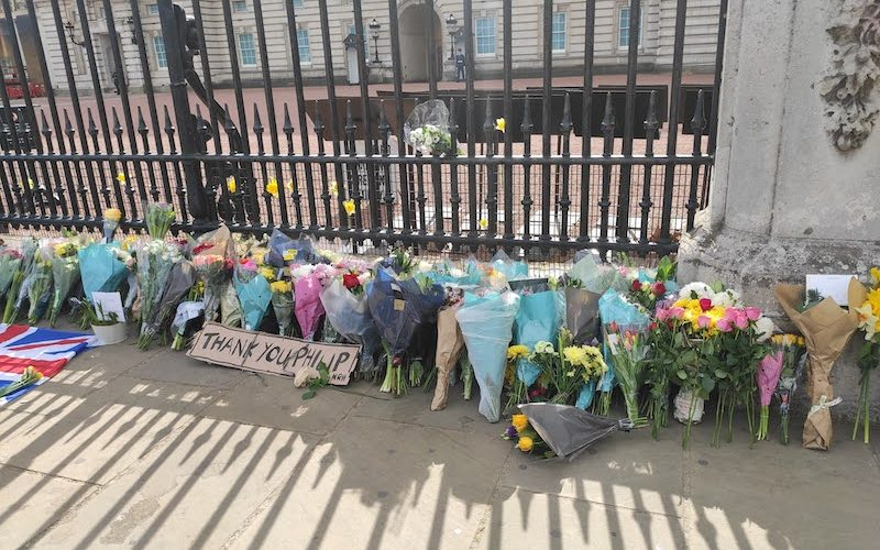 "Flower bouquets lay outside Buckingham Palace. A cardboard sign reads ""Thank you Philip"""