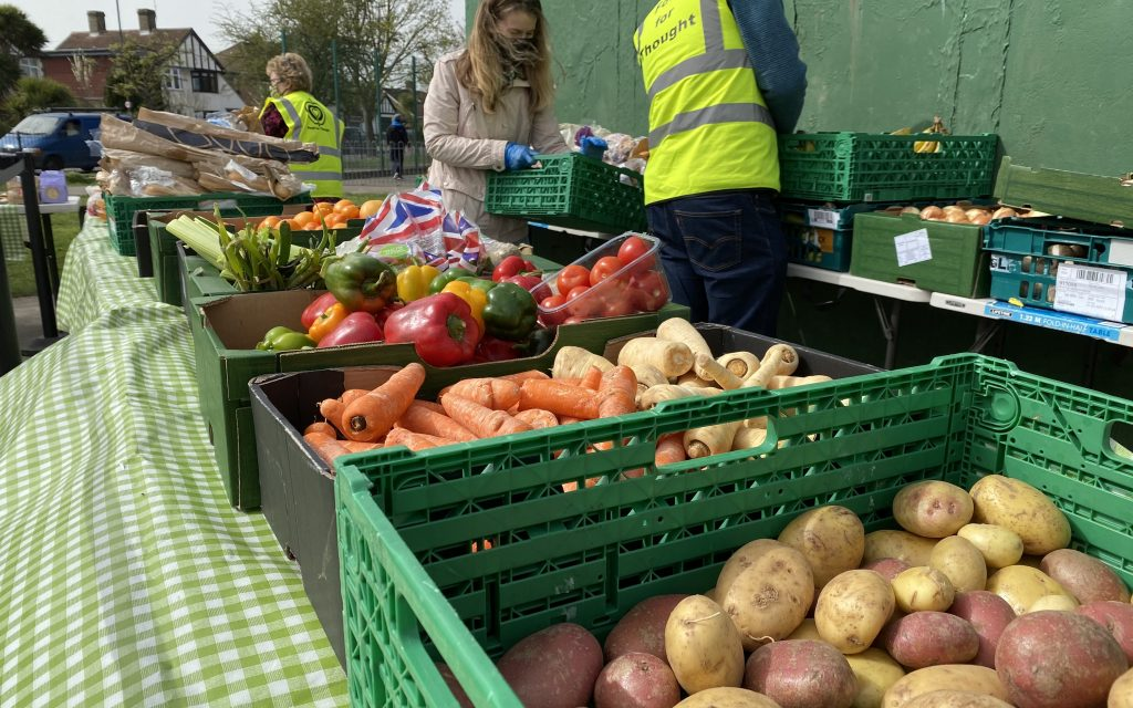 A long table with various boxes containing carrots, potatoes, peppers and other vegetables on display. Behind are 3 volunteers in green vests sorting the produce for customers.