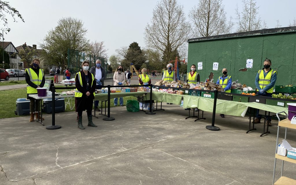 Wide angle shot showing the stall setup in its entirety. The 9 volunteers are standing behind the tables, posing for the photo. It is late afternoon and everyone is observing social distancing as well as wearing their masks and green vests for visibility.