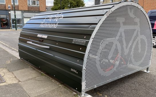 Side shot of the green half cylindrical bike hangar installed on a road. The hangar features an image of a bike on its side and has a metal lid in the centre.