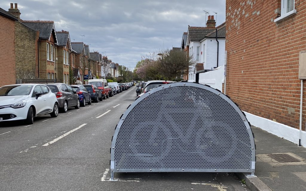 Side view of the bike hangar. It is placed on the right side of a street with cars lining the street on either side. It only takes a half of a lane up in size.