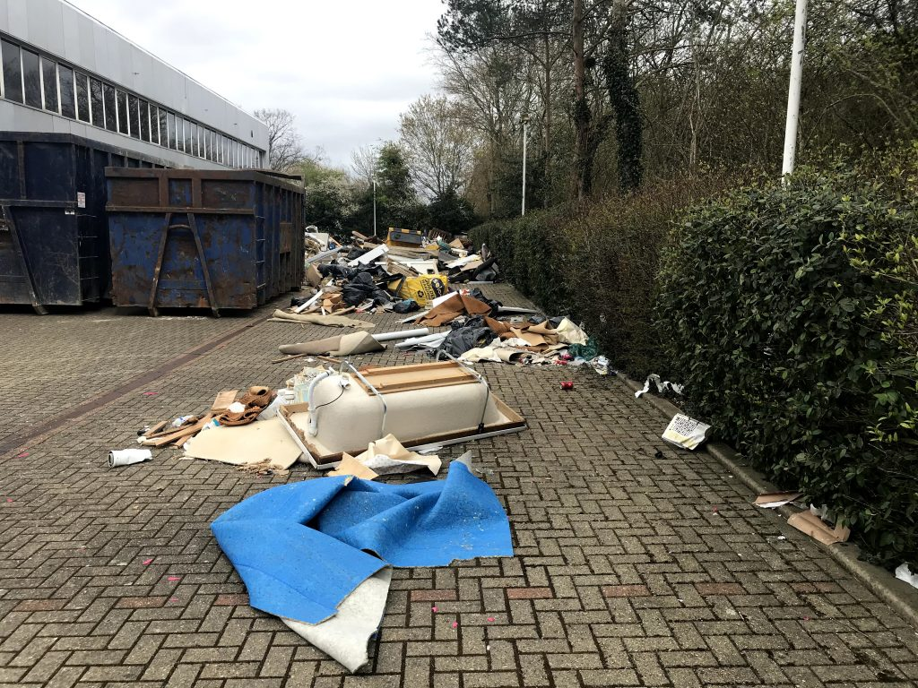 Bathtub and tons of other flytipped rubbish pictured next to industrial skips used for clearing.