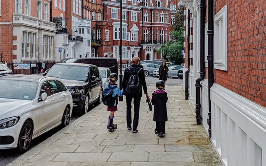 An adult and two children walk along Kensington street on a cloudy day