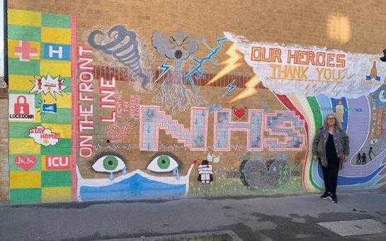 An NHS Mural which celebrates 'NHS heroes' and contains images of storm clouds,. eyes cryng behind a mask an a stone heart paying tribute to 'fallen heroes'. Suzanne Lazenby, the mural's creator, is also pictured.
