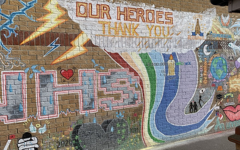"""The NHS mural with detail of tributes to the over 100,000 people killed by COVID-19 in the UK and a stone heart with the words """"Lest We Forget"""" inscribed onto it."""
