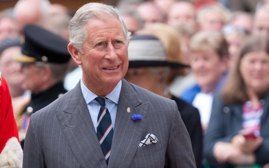 Prince Charles walking. A crow of people stand behind him