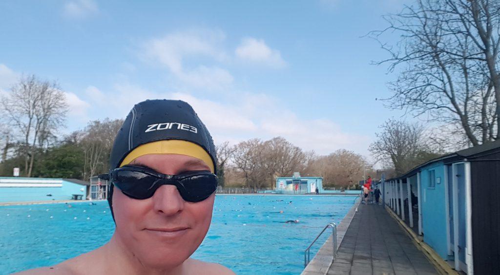 Swimmer wearing swimming hat enjoys Tooting Lido