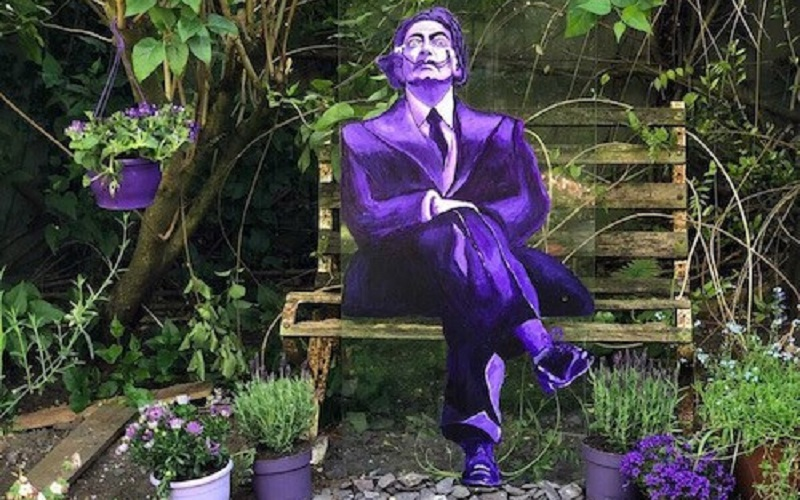 Salvador Dali painted on glass seated on a bench in the garden