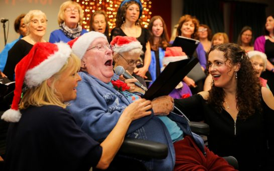 Sarah Cay holds the microphone to an old man who is singing in a chair while wearing a Christmas hat, Sarah is also singing. Choir of mixed ages sings behind him. A lady in a Christmas hat holds the music to him also singing.