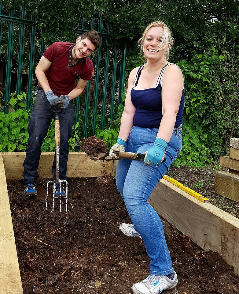Ginnett and a member of the public holding pitchforks in a flower bed looking tired but ecstatic