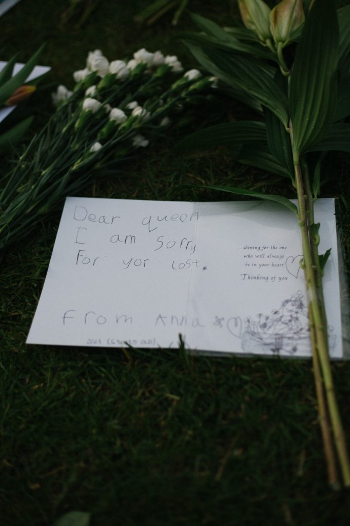 A note and flowers on the ground at Windsor Castle.