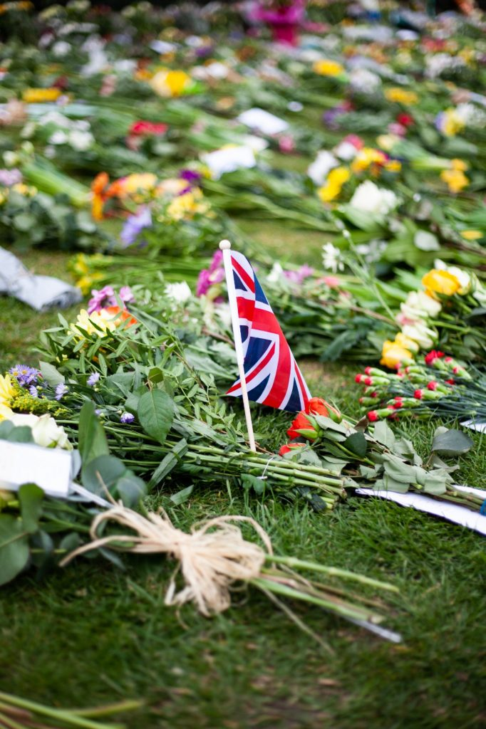 A note, flowers and a small Union flag on the ground at Windsor Castle.