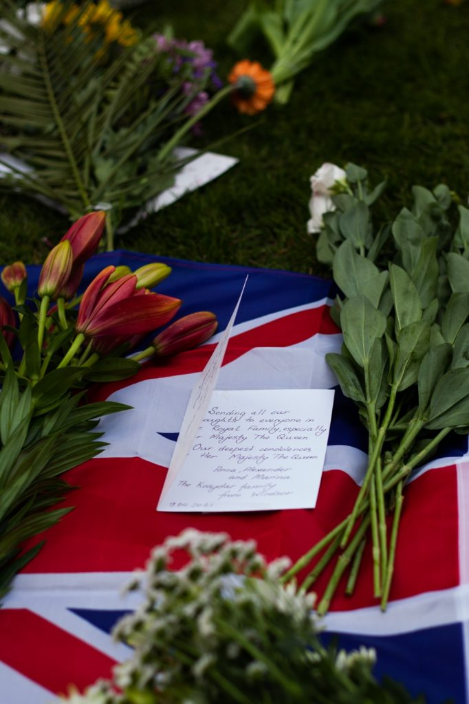 A note and flowers on a Union flag on the ground at Windsor Castle.