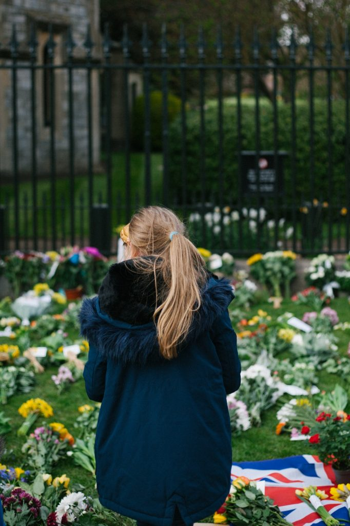The back of a young girl in a blue coat looking at the flowers on the ground.