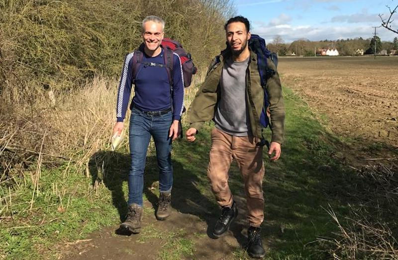 Yusuf and Jon on a hiking trip before lockdown. Both are smiling and have backpacks.