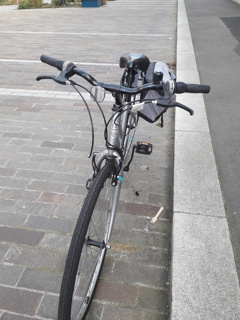 A silver ladies bike parked up next to the pavement with panniers attached.