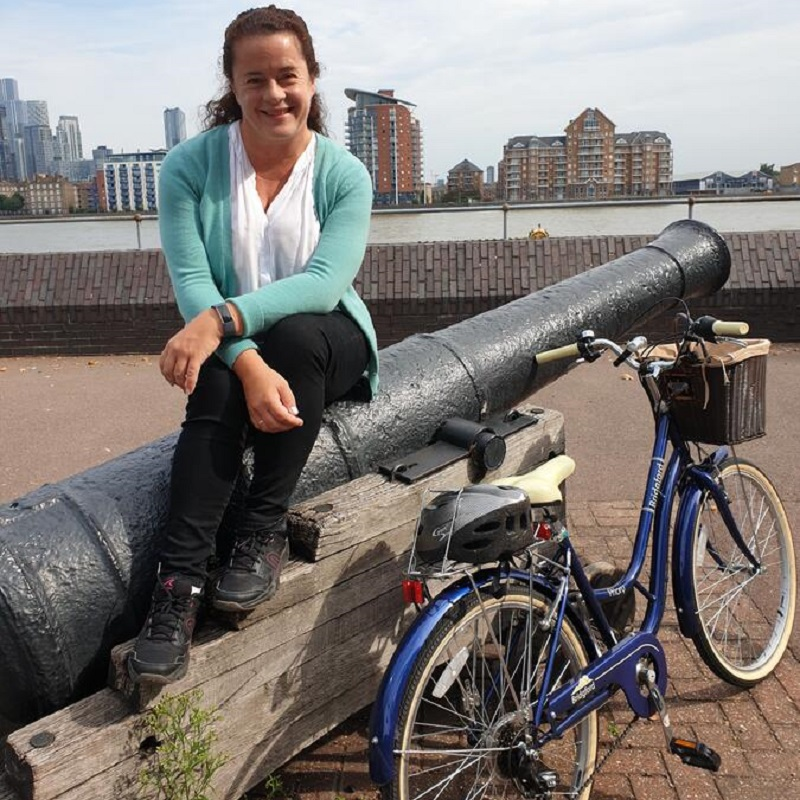 Joanna wears a teal cardigan while sitting on a cast iron cannon by the Thames, with her cream seated electric blue bike leaning next to her.