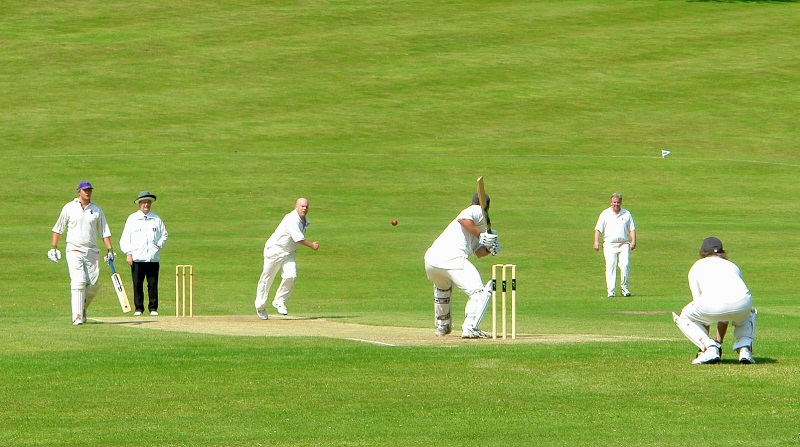 bowler delivers a full length ball pitched at off stump to a batsmen waiting to hit his shot, with a wicket keep tucked behind, in a lush green setting