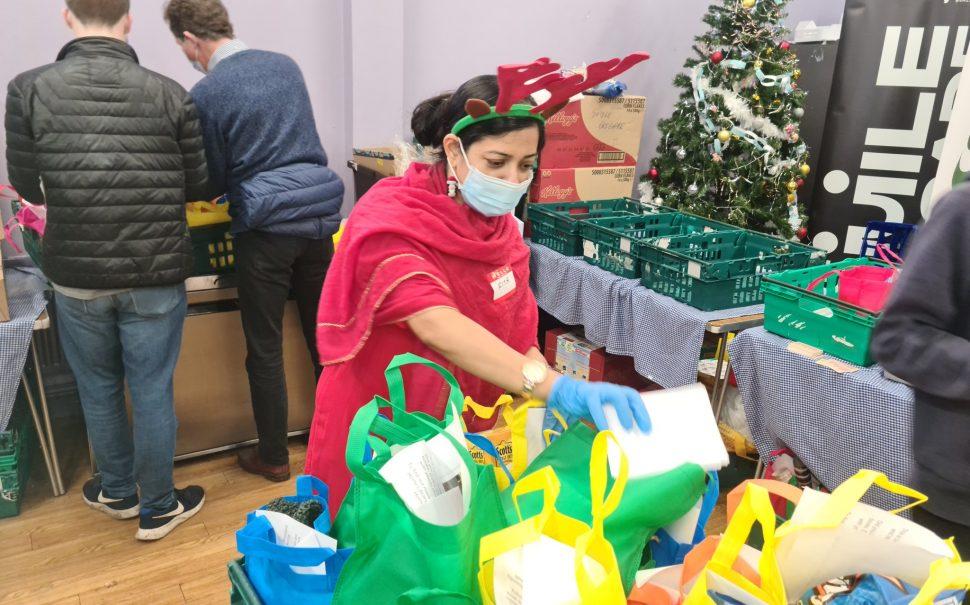 Rita wears reindeer antlers whilst preparing food packages on Christmas Day