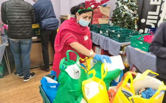 Rita wears reindeer antlers whilst preparing food packages on Christmas Day