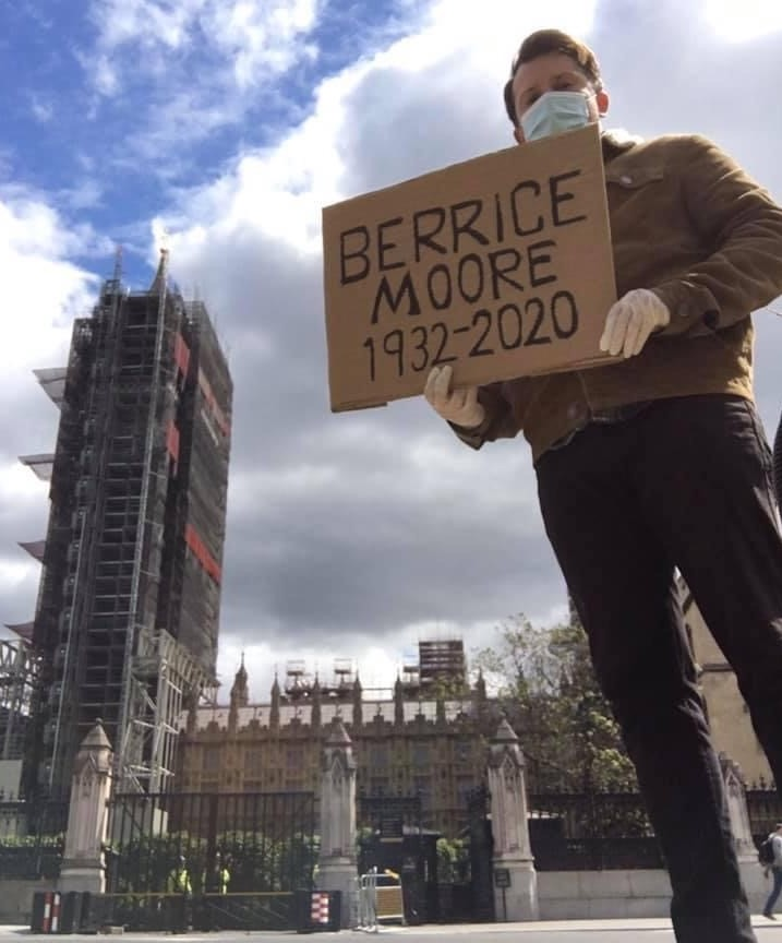 Ellis Tustin holds a cardboard headstone dedicated to his late grandfather Berrice Moore whilst standing outside the Houses of Parliament
