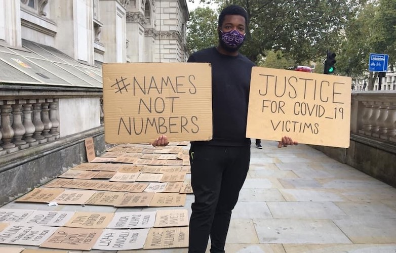 A campaigner holds plaques bearing the slogans #NamesNotNumbers and Justice for Covid-19 Victims