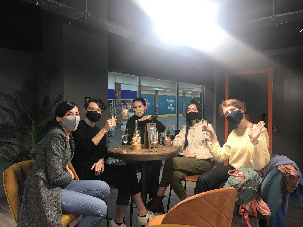 A group of five people toast successfully escaping the Alice in Puzzleland escape room with prosecco at high bar stools.