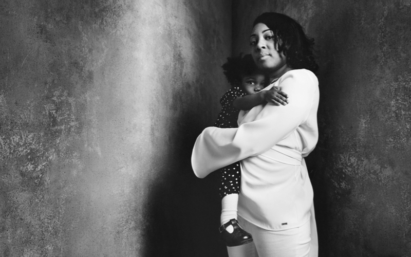 Woman holds her child in a dark room with bare walls
