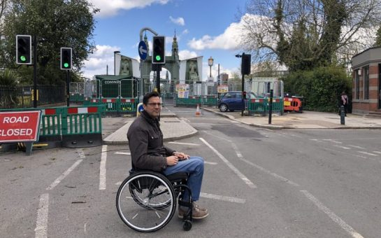 Wheelchair user in front of Hammersmith Bridge