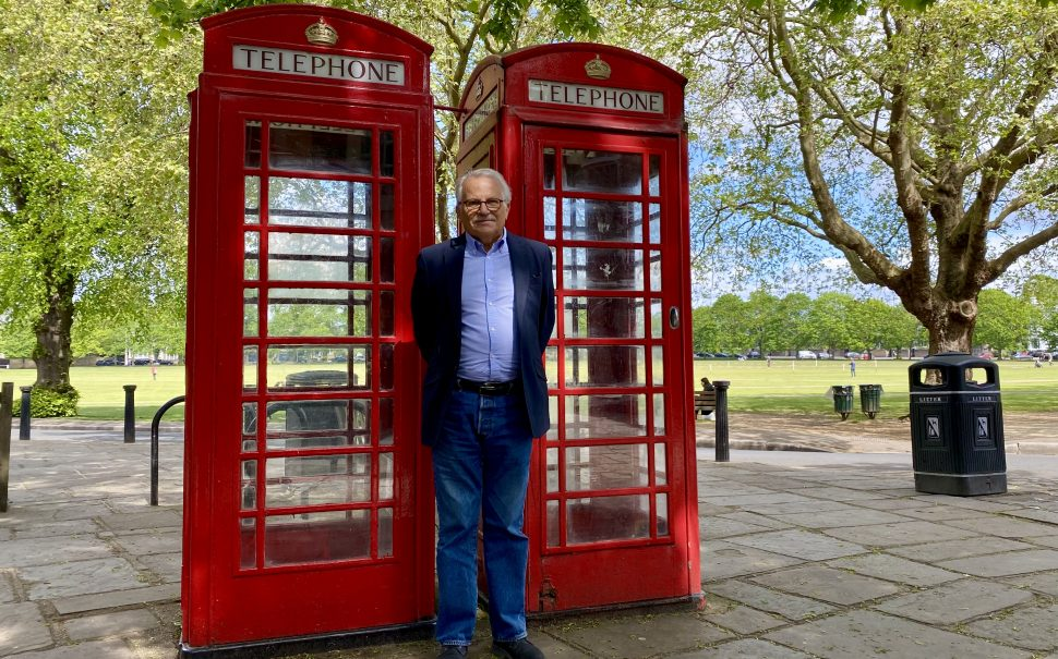 Chairman of Richmond Society, Barry May, standing in a shaded spot under a tree in front of two red English phone booths. The booths are the well known booths that are synonymous with the UK. Behind them is a park which has the sun casting on it.