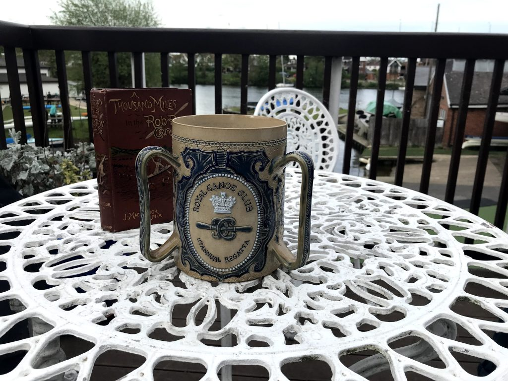 Ceremonial ceramic cup with the Royal Canoe Club logo embossed on it for its annual regatta. Showing the history of the club. Also a first edition copy of A Thousand Miles by John MacGregor who was an explorer who founded the club.
