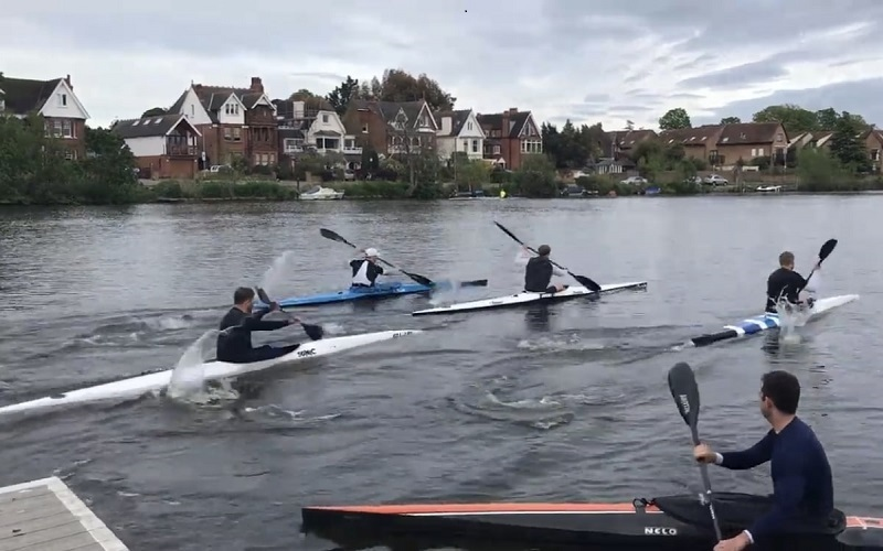 Four kayakers paddling on the Thames by Royal Canoe Club on Trowlock Island in Teddington.