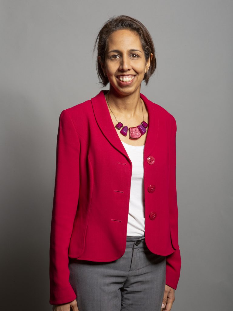 Munira Wilson portrait. She is wearing a pink jacket and grey trousers and is smiling.