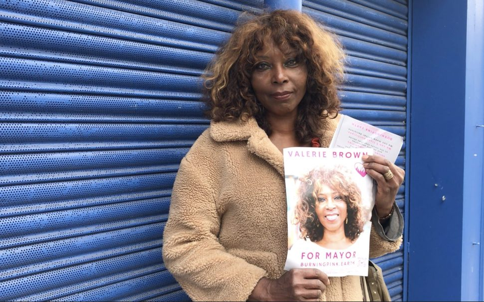 Valerie Brown Burning Pink Party Mayoral Candidate holds up her poster for upcoming elections