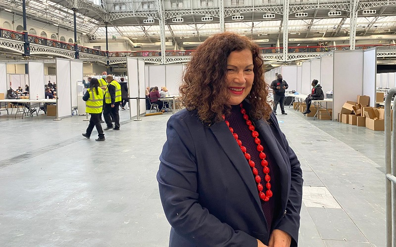 leonie cooper in a blue blazer and red jewellery