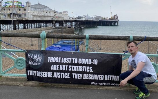 Ellis Tustin crouches with his banner in front of Brighton pier.