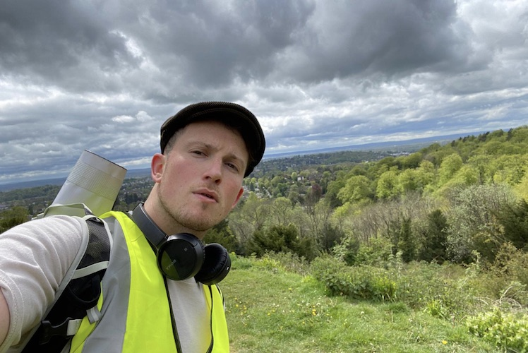 Ellis Tustin takes a selfie in a field during his journey from Fulham to Brighton