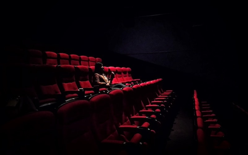 A person sat in a cinema on a red seat watching a film with nobody else in the room with them
