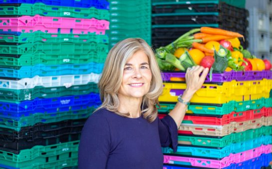 Laura Winningham stands in front of crates of vegetables stacked
