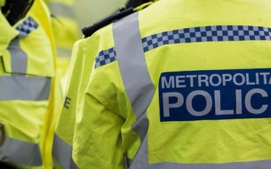 View of the back of police officer wearing a high vis Metropolitan police jacket