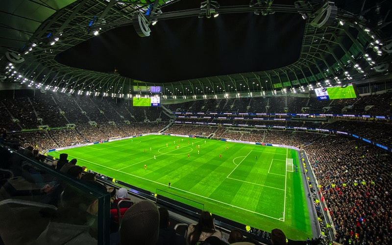 An image of fans in a stadium watching a football match at nighttime