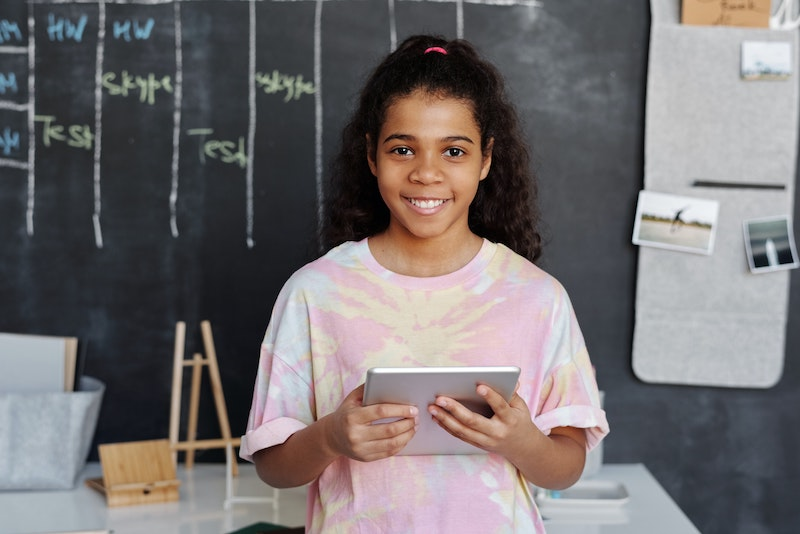 picture of a girl holding a device. Behind her is a blackboard. She is wearing a tie dye shirt.