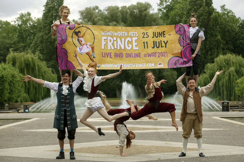 A troop of performers hold a banner advertising the fringe.