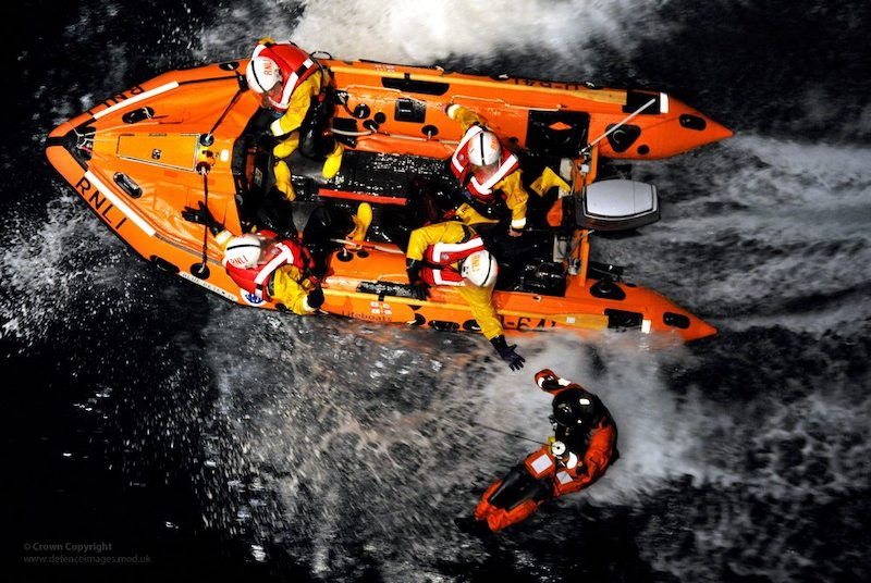 RNLI crew members carrying out a rescue. Shot from above.